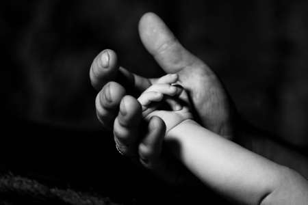 hand of an adult and  child in dark vein photo