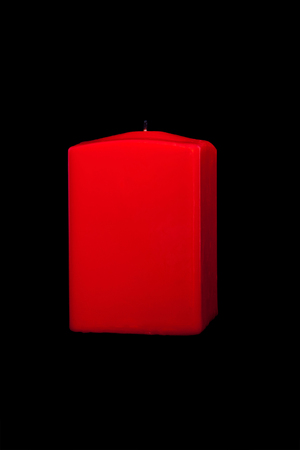 burned out: red candle on black background