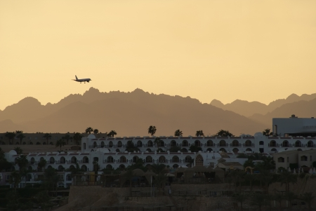 plane lands on the background of the mountains and the hotel
