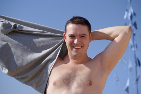 the young man takes off his shirt to swim Stock Photo - 14666062