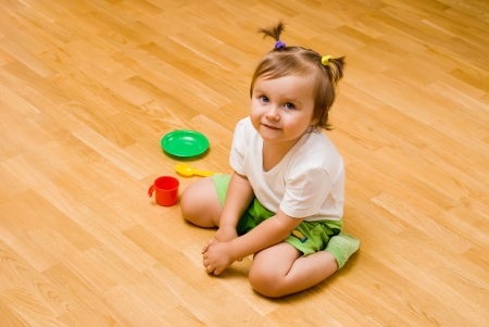 little girl sat on the floor with toy tea things Stock Photo - 15072955