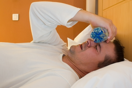man with bottle and flu and he has a temperature Stock Photo