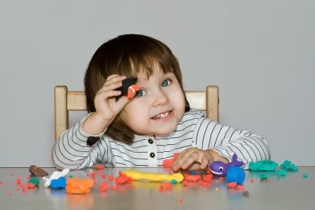 portrait little girl is playing with colorful dough isolated on gray background Stock Photo - 17190222