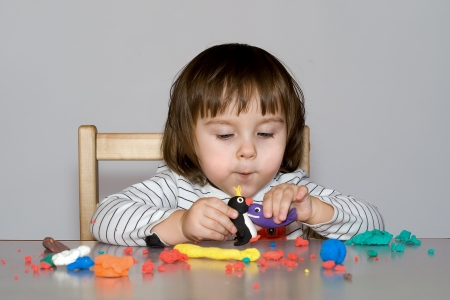 portrait little girl is playing with colorful dough isolated on gray background Stock Photo - 17190223