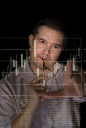 young man in pink shirt as a trader measures fingers candle stick graph to analyze stock over black background Stock Photo