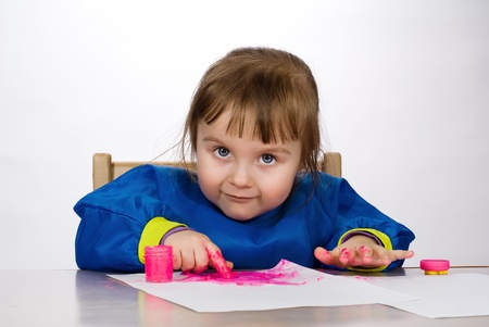 Little girl painting finger paint on paper