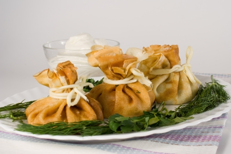 Bags of pancakes decorated with cheese and herbs in white plate