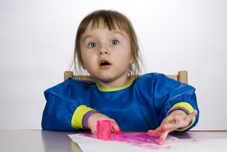 Little girl painting finger paint on paper and stares out