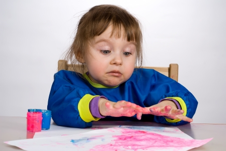 Little girl stare with astonishment at color fingers