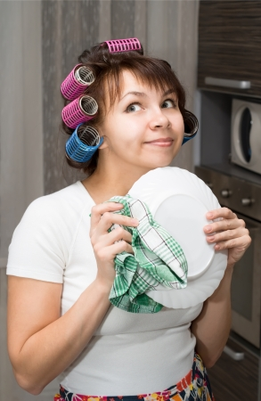Housewife wipes plate and dreams in kitchen