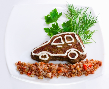 The car-shaped liver pancake with buckwheat porridge for children Stock Photo