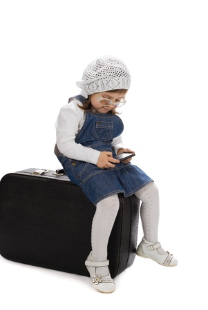 Sitting on a suitcase girl playing with phone Stock Photo