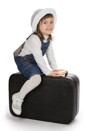 Smiling little girl sitting on a suitcase with small book