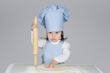 Beautiful little girl masrer chief cooking pizza over gray background photo