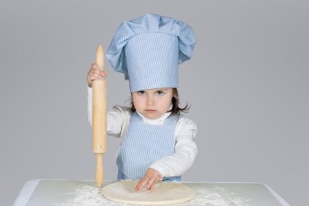 Hermosa ni�a masrer jefe de cocina la pizza sobre fondo gris photo