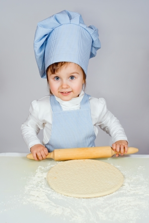 Pretty little girl chief cooking pizza over gray background Stock Photo