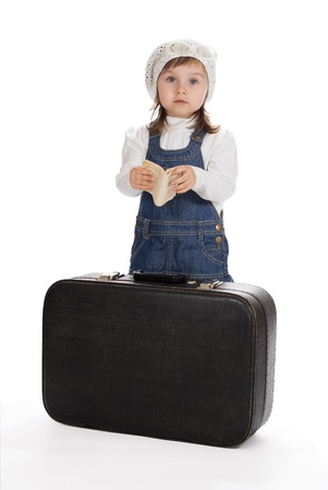 Pretty little girl with book and suitcase isolated on white