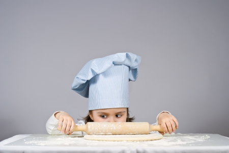 Beautiful little girl cooking pizza over gray background