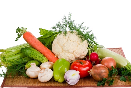 different fresh vegetables on bamboo mat over white background Stock Photo