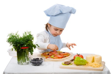 little girl preparing a pizza with cheese and vegetables