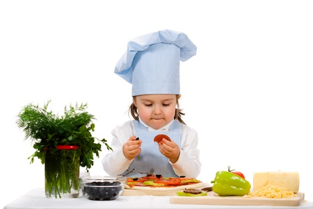 making fun: little girl preparing a pizza with salami and vegetables