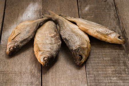 Four dry fishes on wooden table