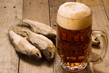 Pint of beer and dried fishes on wooden table Stock Photo