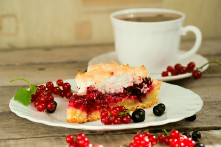 Piece of berry pie, red and black currants on white plate and wooden table