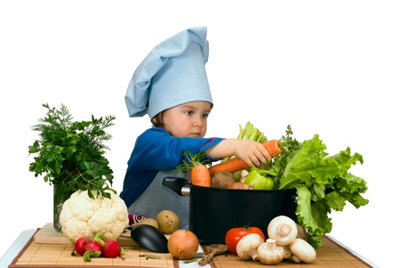 Cute little girl cooking soup with lots of different vegetables Banco de Imagens