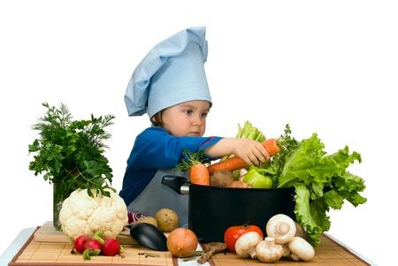 niños cocinando: Poco de sopa para cocinar linda chica con un montón de diferentes verduras Foto de archivo