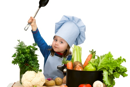 Cute little girl cooking soup with lots of different vegetables photo