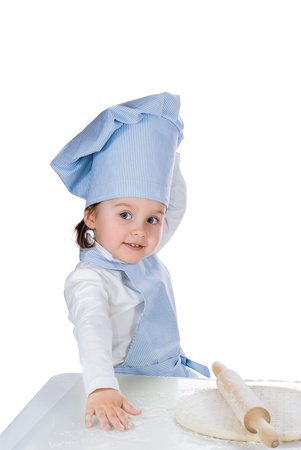 Little girl dressed as a cook posing with pizza dough
