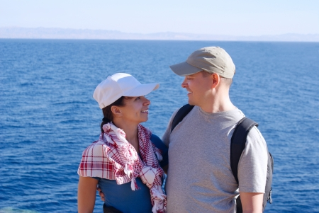 Portrait of happy young women in arabian scarf and man with backpack outside on coast over blue sea and sky Stock Photo