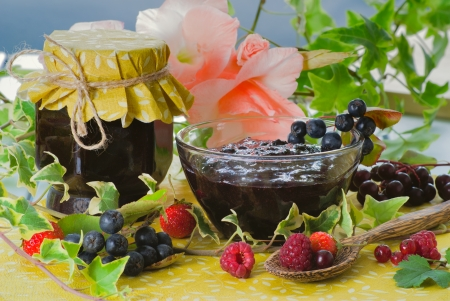 Fresh homemade chokeberry confiture in glass served with different berries