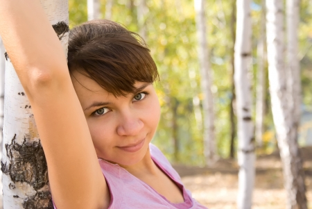 Horizontal portrait of beautiful brunette girl in the forest standing near birch Stock Photo