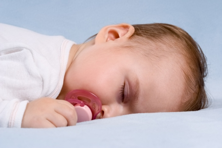 Close-up portrait of a beautiful sleeping baby on blue blanket  Use the photo to represent life, parenting or childhood
