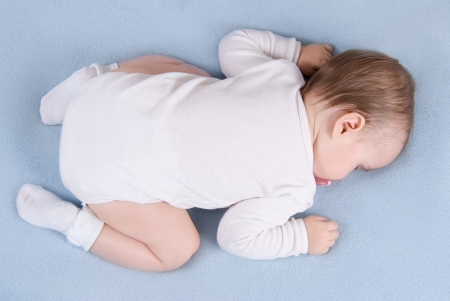 Baby sleeps on soft blue blanket  Top view photo