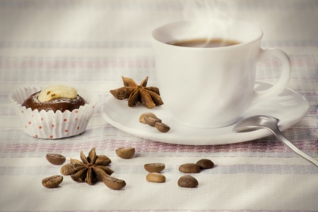 Cup of coffee decorated beans and star anise with fresh almond cake on a striped napkin  Morning concept  photo