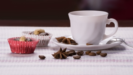 Cup of coffee decorated beans and star anise with fresh almond cakes on a striped napkin  Morning concept