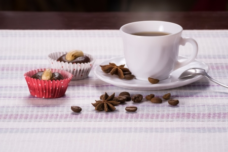 Cup of coffee decorated beans and star anise with fresh almond cakes on a striped napkin