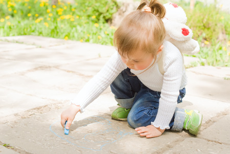 hellion: Cute little girl drawing with blue chalk outdoors
