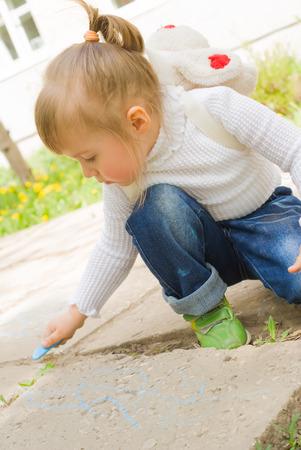 2 to 3 years: Cute bambina disegno con il gesso blu all'aperto