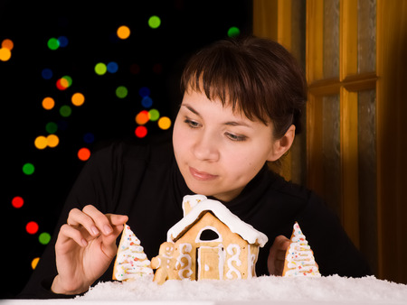 Young woman decorating gingerbread house