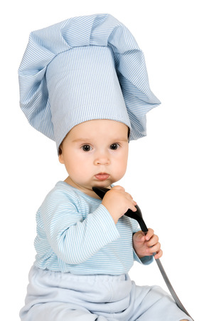 Little child with metal ladle and cook hat as a cook photo