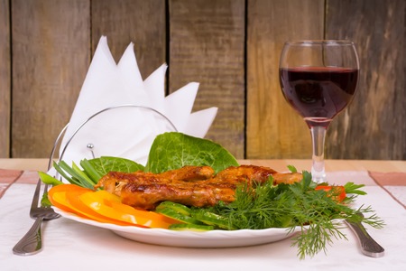 Grilled Chicken Tapakats (Tabaka) with vegetables and glass of red wine on table in wooden restaurant interior. Georgian cuisine, selective focus on the dish. Stock Photo