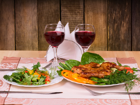 Grilled Chicken Tapakats (Tabaka) with vegetables and glass of red wine on table in wooden restaurant interior. Georgian cuisine, selective focus on the dish. photo