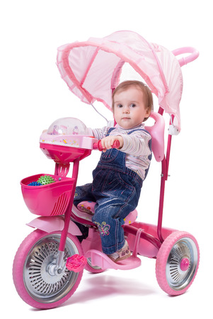 Portrait of little girl riding a children trike  Isolated on white background photo