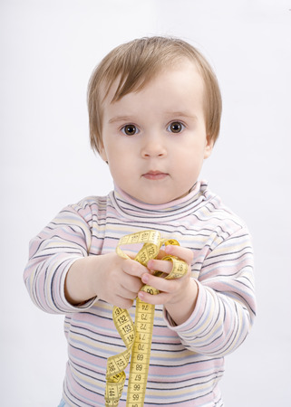 Adorable baby girl with a measuring tape in hands Stock Photo