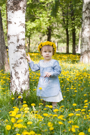 Pretty toddler girl with floral head wreath on the meadow with yellow flowers photo