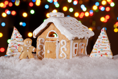 Gingerbread house with gingerbread man and christmas trees  Gingerbread man cookie standing in snow beside house  Christmas decoration  photo